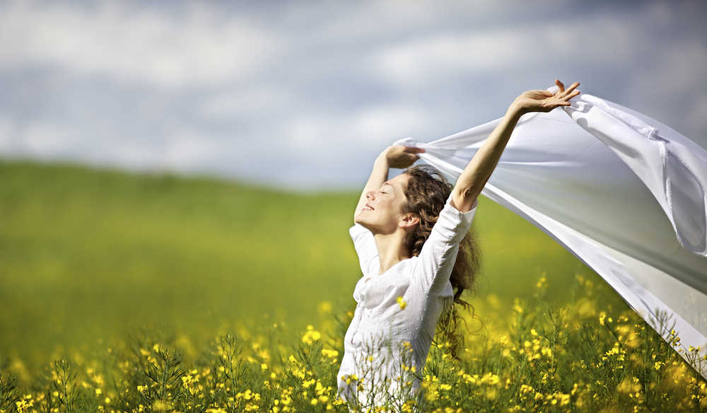 Young happy woman standing in yellow rapeseed field holding a white piece of cloth in the wind expre